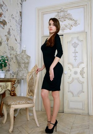 Femme fatale in a sexy black dress is a utterly excited person undressing before mirror