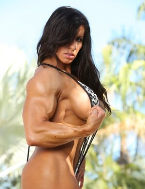 Black-haired dame bodybuilder seductively undresses by poolside