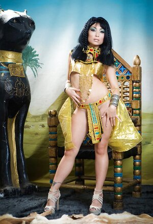 Asiatic girl plays the role of Cleopatra posing on a golden throne