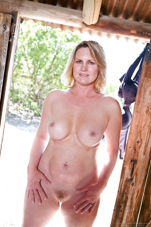 Mature throws panties out the door, hangs a bra, and poses in the wooden barn