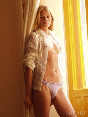 Innocent blonde in sexy shirt and panties relaxes nude near balcony door