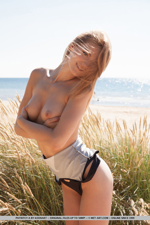 Magnificent model takes off one-piece swimsuit and poses on a windy day
